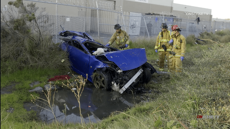 Chula Vista firefighters examine wreck of Nissan at scene of accident.