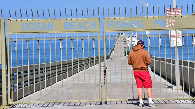 A young man finds the Ocean Beach Pier closed due to city policies requiring social distancing.