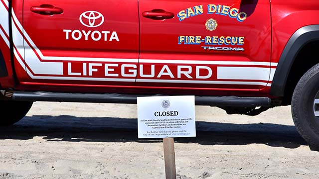 Lifeguards enforce the closure of city beaches.