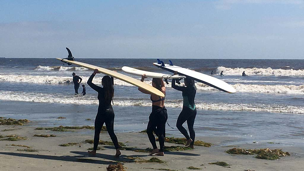 Three woman surfers head for the waves at Tourmaline Beach in La Jolla