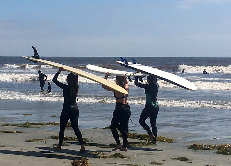 Three woman surfers head for the waves at Tourmaline Beach in La Jolla