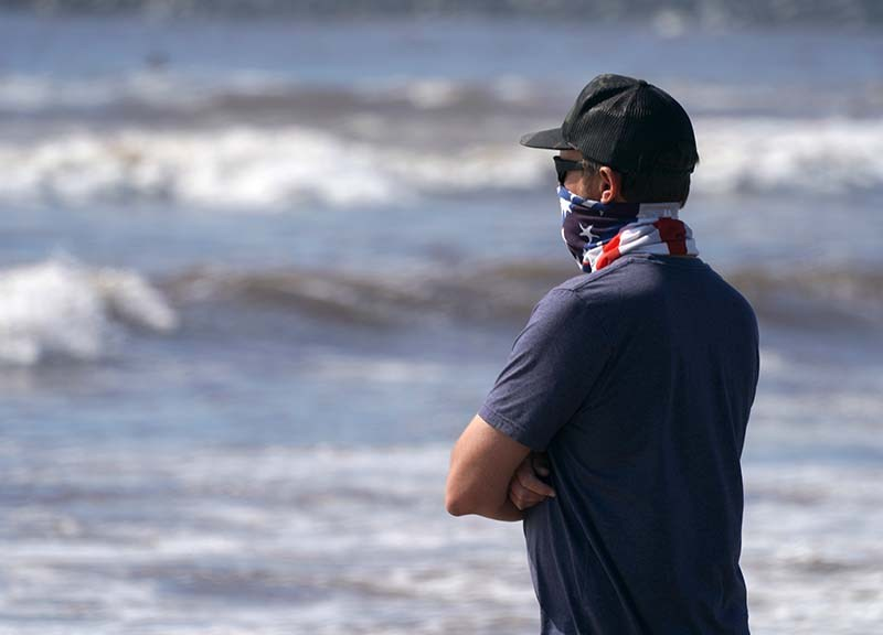 A man, one of fewer beachgoers to wear a mask, watches his child in the water.
