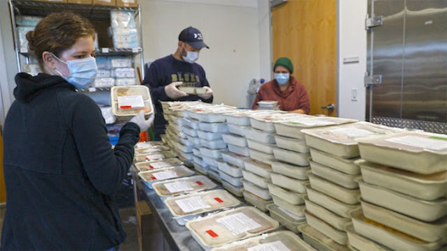 Volunteers sort frozen meals for isolated adults