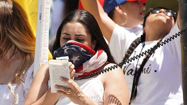 Protest organizer Naomi Soria reads from a pocket Constitution in Pacific Beach