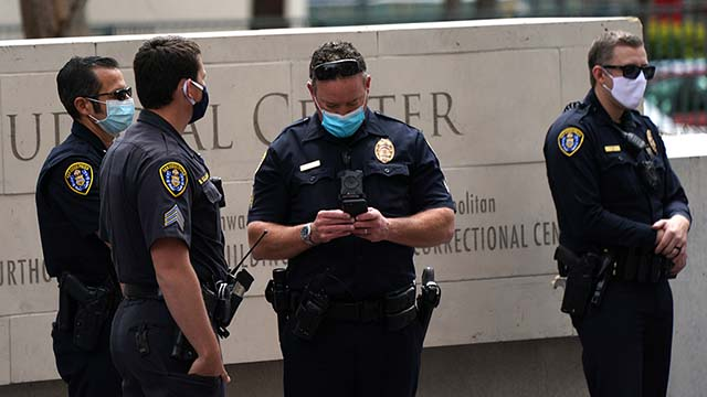 """San Diego police kept their distance across Broadway during Saturday """"freedom rally"""" seeking reopening of the state economy."""