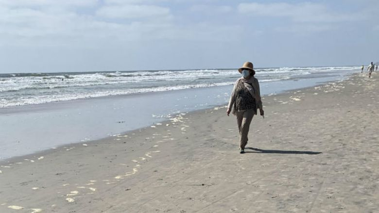 Woman in face mask walks on the beach