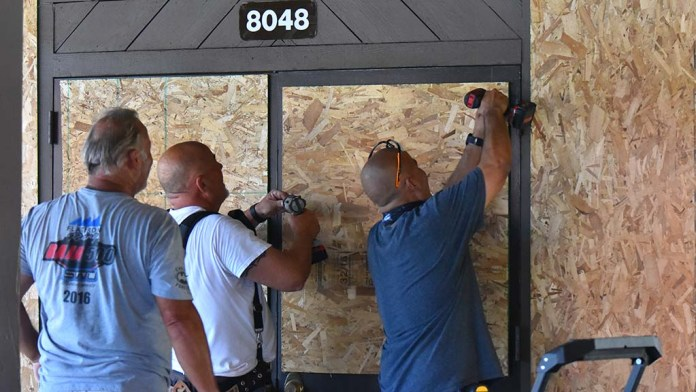 La Mesa residents climb broken windows and doors at the La Mesa Springs Shopping Center, where people loot and break windows.