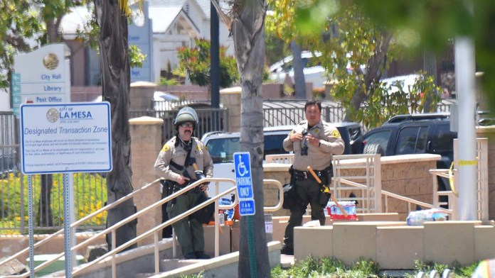 Two sheriff's deputies guard the entrance to the La Mesa police department on Sunday.