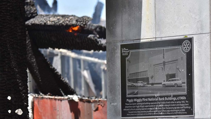 A La Mesa Historical Society placard remains in front of a burning building that is used by Randall Lamb as a business engineering consultant.