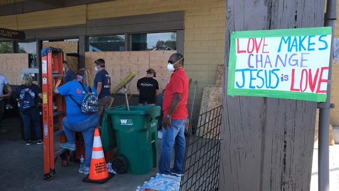 More than 1,000 volunteers gathered to clean and repair damage in downtown San Diego, including at Play It Again Sports at La Mesa Springs Shopping Center.