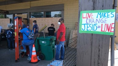 More than 1,000 volunteers gathered to clean up and repair damage in downtown San Diego, including at the Play It Again Sports in the La Mesa Springs Shopping Center.