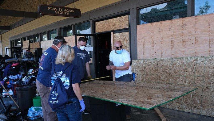 Volunteers cut plywood to climb to the window which was destroyed by protesters at La Mesa Springs Shopping Center on Saturday night.