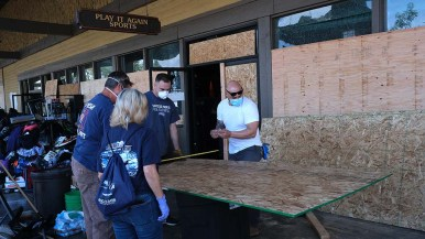 Volunteers cut plywood to board up windows smashed by protesters at the La Mesa Springs Shopping Center Saturday night.