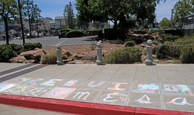 """A colorful chalk message, """"Rebuild La Mesa"""" was drawn next to a parking lot with two banks that were burned to the ground by protesters."""