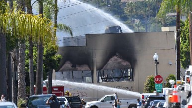 Firemen put out smoldering material in a burned building in downtown La Mesa Sunday morning.