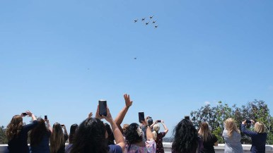 Atop a parking garage at Sharp Grossmont Hospital in La Mesa, healthcare workers cheer U.S. Air Force Thunderbirds during flyover just after noon.