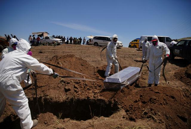 Gravediggers in protective suits bury a coronavirus disease victim