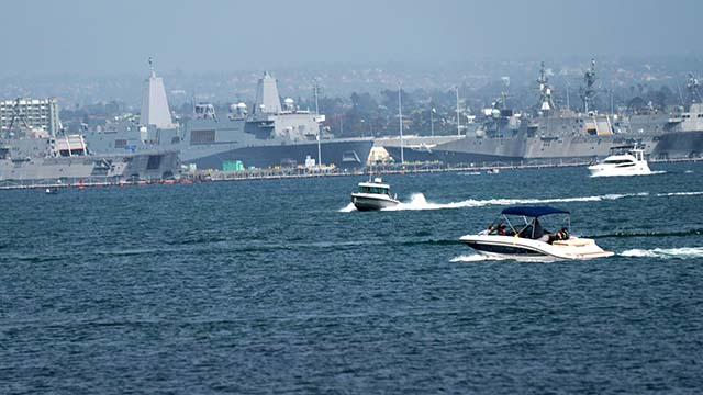 Pleasure watercraft speed through Coronado Bay with Navy littoral ships in the background at Naval Base San Diego.