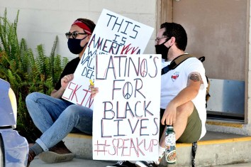 Protester rests with his sign: Latinos for Black Lives.