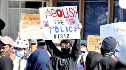A sign using the number 1312, slang for police, is held at La Mesa protest.