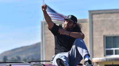 Outside La Mesa City Hall, a protester makes a fist while sitting on a car painted with slogans.