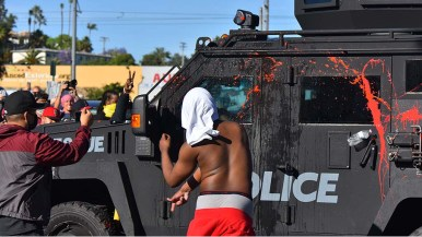 Protester in red shorts throws a water bottle at police vehicle as it was backing up toward Allison Avenue.
