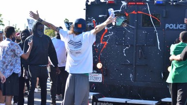 A protester stands behind a police armored vehicle backing up toward Allison Avenue in La Mesa.