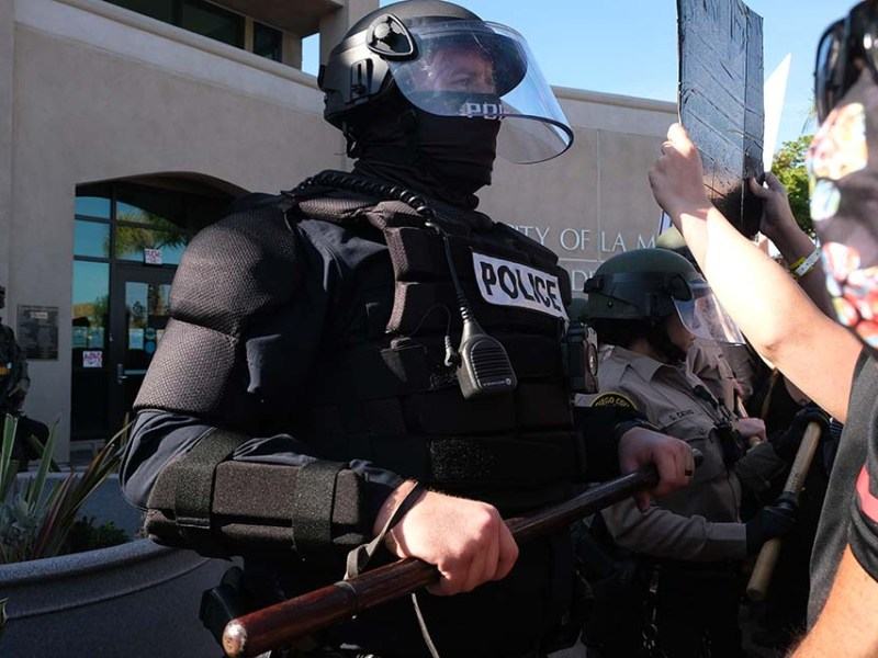 A protester presents a sign to a well-armored La Mesa police officer. Photo by Chris Stone
