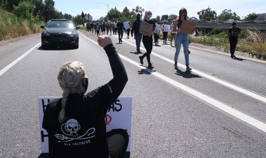 A woman sat down on La Mesa Boulevard onramp to Interstate 8 as other protesters walked past.