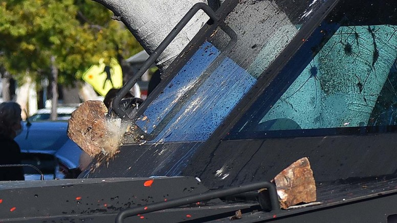 Rock grabbed from nearby landscaping smashes into police armored vehicle.