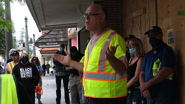 La Mesa attorney Scott McMillan leads a discussion of La Mesa Civil Defense volunteers near Swami's Cafe on June 5.