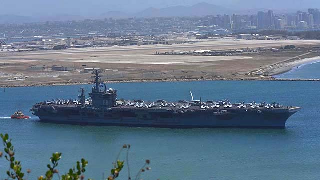 The USS Nimitz heads out of San Diego Bay for deployment with about 5,000 troops on board.