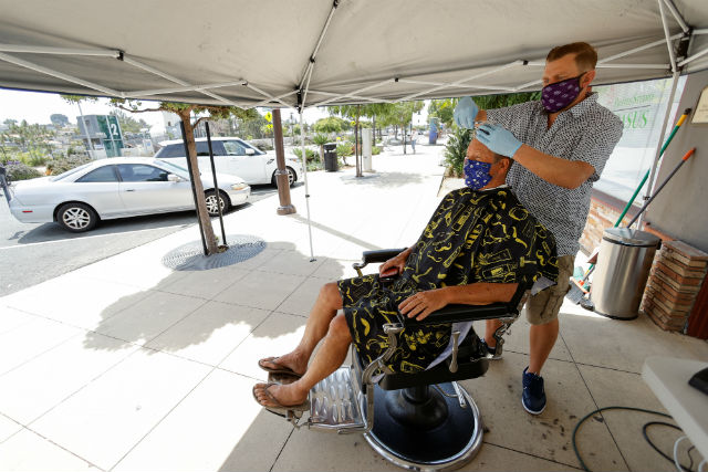 A barber in Solana Beach cuts hair on the sidewalk