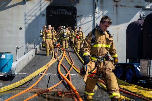 Firefighters leaving the USS Bonhomme Richard