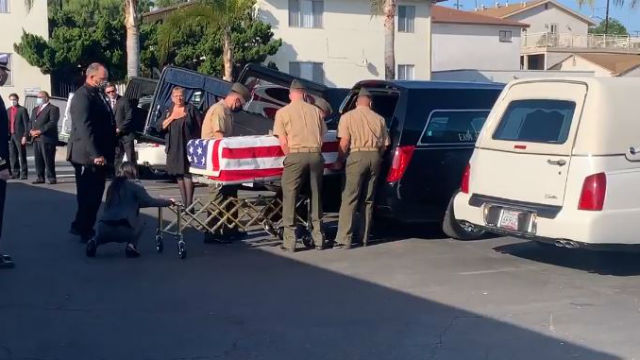 Remains of victim are placed into a hearse
