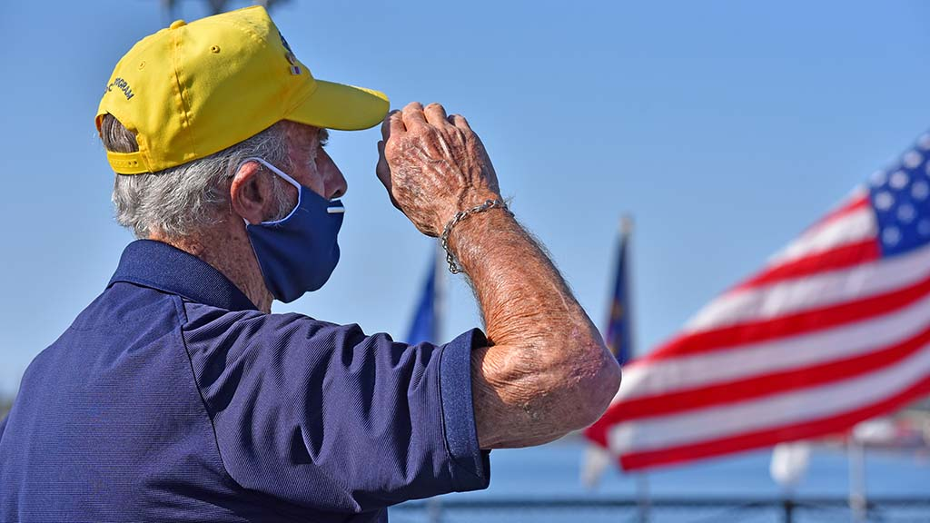 World War II veteran Al Hansen salutes the American flag during the playing of the National Anthem.