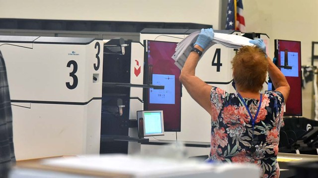 Lastly, stacks of ballots are loaded into ballot tabulating machines.