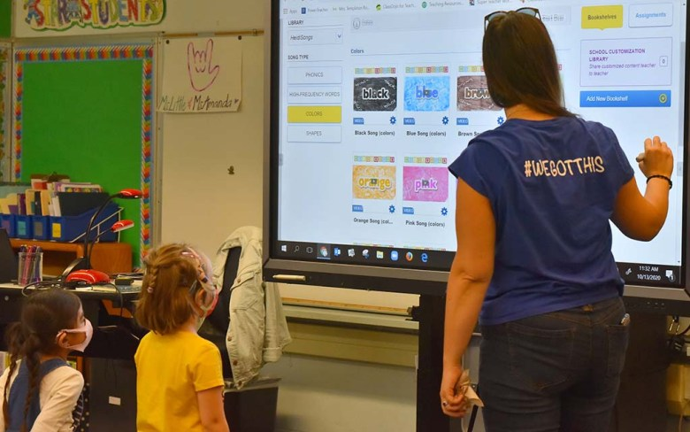 A teacher at Lafayette Elementary School teaches two of her students on the first day back to school since March.