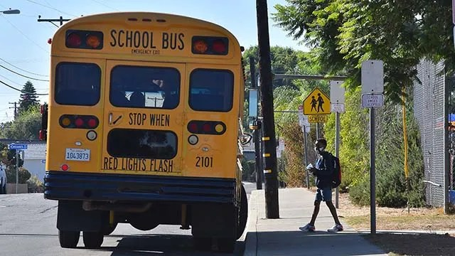 A student gets on a bus after attending a two-hour in school session at Lafayette Elementary School in Clairemont.
