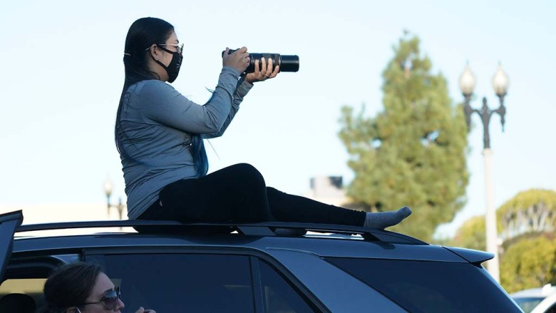 """A spectator at the drive-in performance of """"Nutcracker"""" uses her SUV as a viewing platform to snap some shots of the performance."""