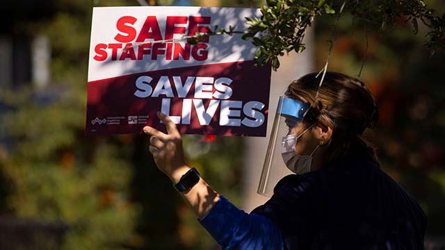 A woman holds a banner as registered nurses at the University of California Irvine Medical Center protest over safety concerns during the outbreak of the coronavirus disease (COVID-19) in Orange, California, U.S., November 10, 2020.
