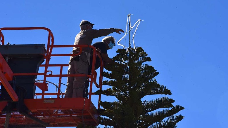 The placement of star was Job 1 for OB volunteers after Christmas tree was placed in its beach home.