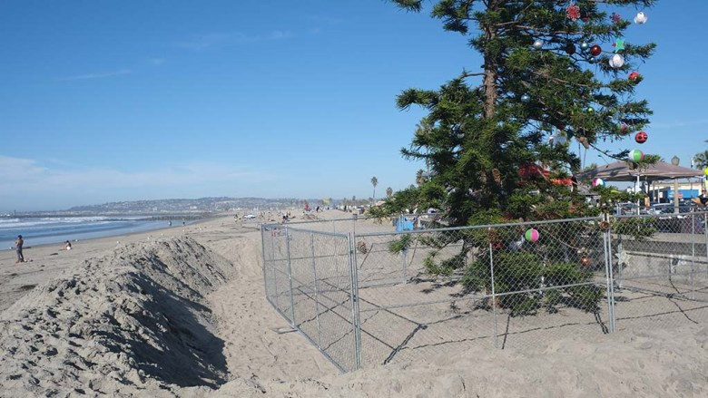 Sand berms were created to protect against high surf and a chain link fence was added to keep people away.