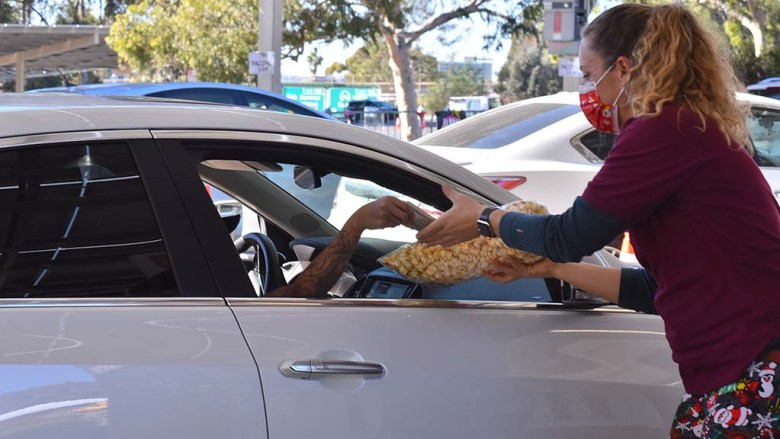 Lisa Porcell sells a bag of kettle corn from a customer at Taste of December Nights across the street from Balboa Park.
