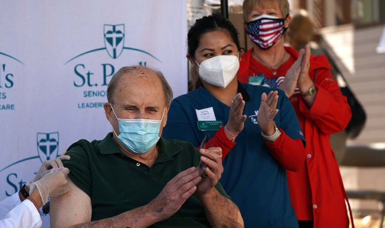 Eldon Thompson, a resident at St. Paul's McColl Health Center, Katrina Longoria, director of staff development and Cheryl Wilson, CEO, applaud as Thompson is the first to be vaccinated at the facility