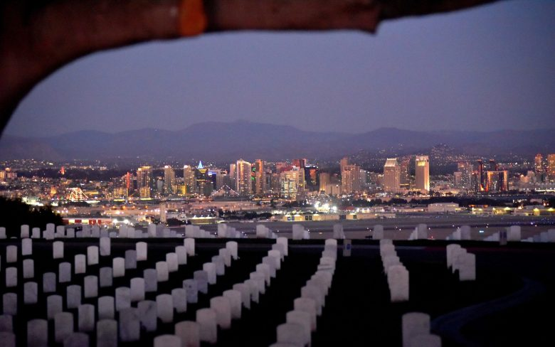 Dusk settles in on downtown San Diego with Fort Rosecrans National Cemetery in the foreground.