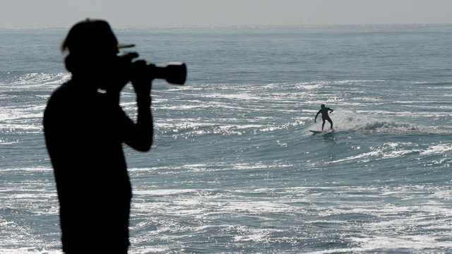 A photographer shoots the wave action in La Jolla as a swell brought elevated waves.