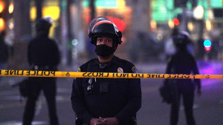 San Diego Police officers put up police tape to limit the areas where protesters could walk.
