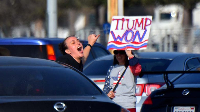 A rider in a passing car shows her enthusiasm to Trump supporters in front of the San Diego County Administration Building on Jan. 6.