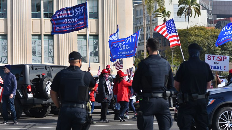San Diego Police officers watch over the protest on the median along Harbor Drive on Jan. 6.